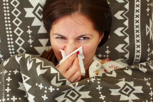 Fotografia, Obraz  Sick young woman in pyjama, laying in bed, covered under duvet, holding tissue handkerchief in her hand to blow runny nose