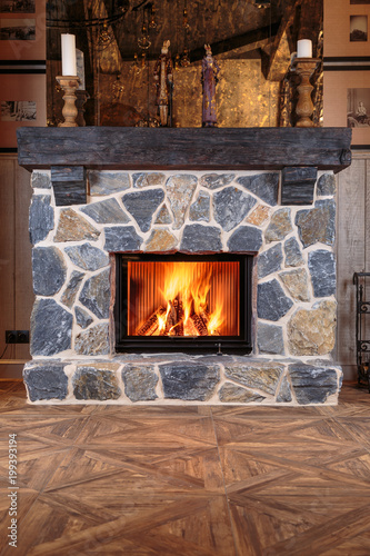 Fotografía blazing fire in the massive fireplace of hewn stone on a beautiful wooden floor
