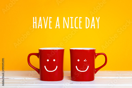 Two red coffee mugs with a smiling faces on a yellow background with the phrase Have s nice day