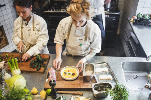 High angle view of female chefs working at kitchen counter in restaurant