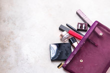 Open Purple Woman's Purse With Glamorous High End Beauty Products From Above On Gray Background. Minimalism Fashion Blogging Concept. Copyspace For Text, Horizontal