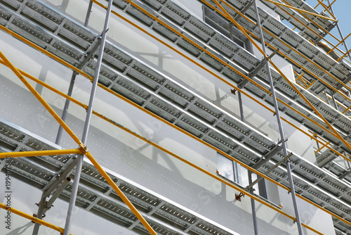 Fotografia scaffolding near a new house, building exterior, construction and repair industr