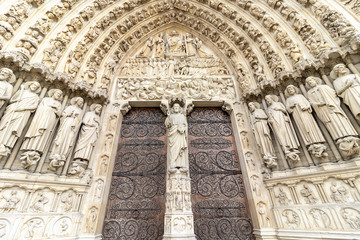 Main Entrance door of  Notre Dame Cathedral in Paris. Ornate Facade with sculptures statues and gargoyles. France