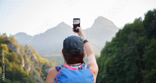 Poster Kaki Picture from back of female tourist photographing mountain
