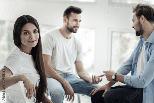 Fototapety, obrazy: Female patient. Nice attractive young woman sitting with other patients and turning to you while having psychological therapy session