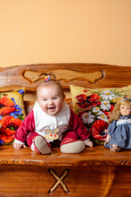 Little Baby With A Tail Sits On A Sofa With Embroidered Pillows And Toys