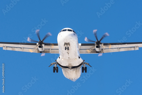 Fotografia, Obraz  Turboprop aircraft with propeller engines on its wings before landing on a runway at the airport against a blue sky