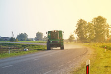 Tractor Rides On The Asphalt Road In The Sunlight