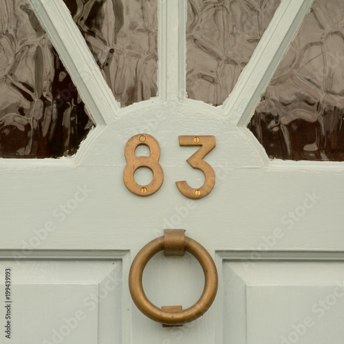 Poster  House number 83 sign on door with brass door knocker