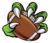 Fototapeta Dinusie - Monster animal claw holding American Football Ball