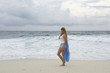 Young woman walks along a deserted beach