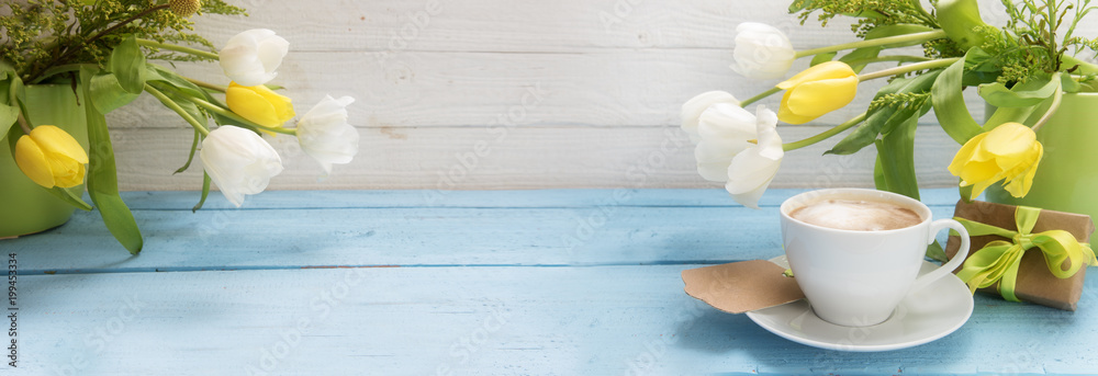 coffee cup, yellow and white tulip flowers in green vases and a little gift on a blue wooden table, panoramic banner format with copy space