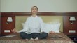 Smiling businesswoman taking yoga lotus position sitting relaxed on bed in hotel room. Travel, business and people concept