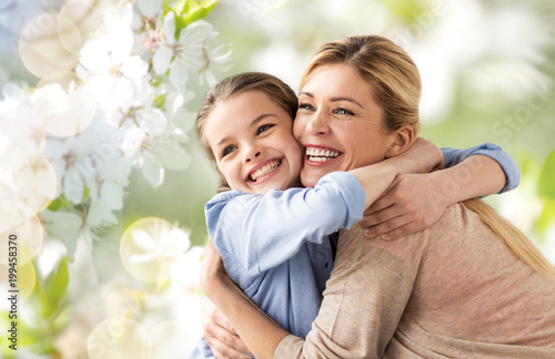 Fotografie, Obraz  people and family concept - happy smiling mother hugging daughter over cherry bl