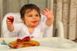 One year old baby boy eating strawberryes and looking at his dirty small hand