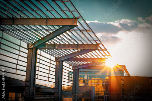 An interesting metal pergola by a downtown building with windows and bright sunglare at sundown Fototapeta