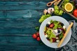 Salad with mozzarella and fresh vegetables. On a blue wooden background. Top view. Copy space for your text.