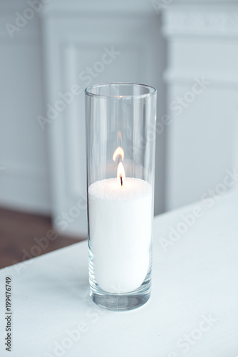 Fotografiet  A burning candle in tall glass vase flask standing on the table indoor