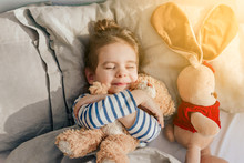 Beautiful Baby Girl Sleeping In My Own Bed At Home With A Favorite Toy Bear.