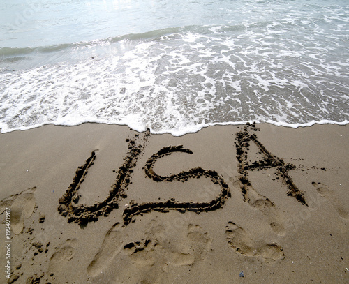 USA text written on the sand of the beach near the sea
