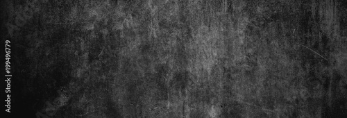 Obraz Textur einer fast schwarzen und alten Betonwand als Hintergrund, auf die leichtes Licht fällt - fototapety do salonu