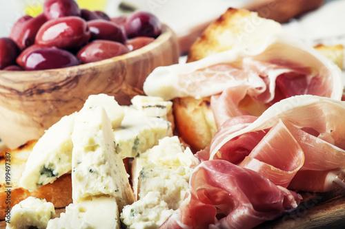 Plakat Przekąski lub antipasti, crostini, prosciutto, ser pleśniowy i oliwki, szare tło, selektywne focus