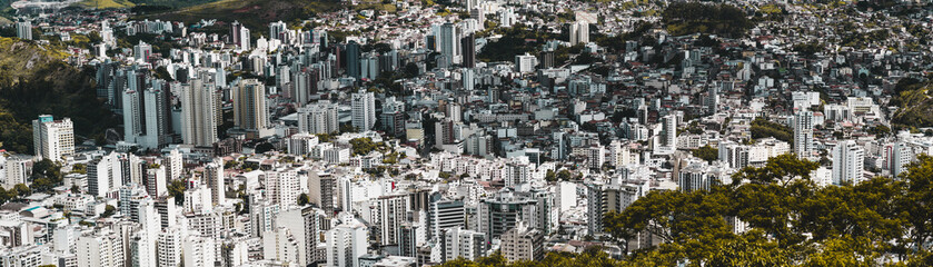 Panel Szklany Panoramic shot of an urban landscape from high above of Juiz de Fora town in Minas Gerais state of Brazil: multiple multistorey residential and office buildings, favelas, parks, and hills, bright day