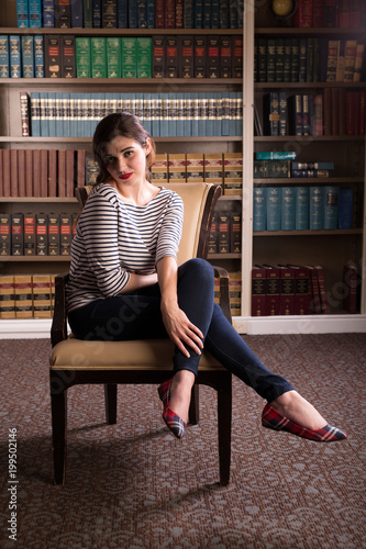 Young caucasian woman dressed in mid century casual fashion poses in a library Poster
