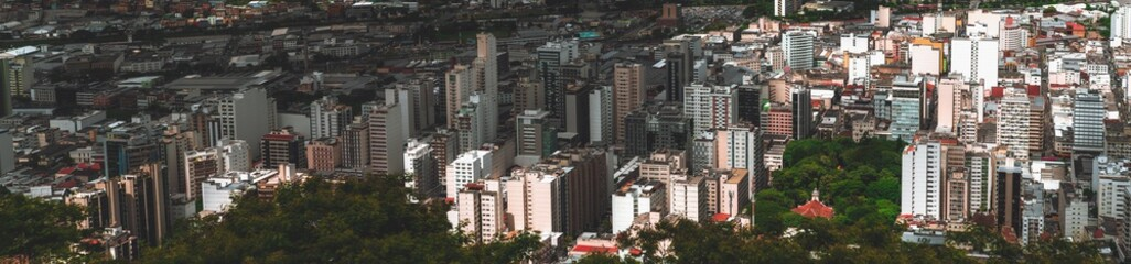 Fototapeta The panorama of Juiz de Fora city in Minas Gerais state of Brazil: plenty of multistorey building, parks, favelas, church, offices, and blocks of flats, chaotic mass scale, roads and streets