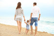 Couple with little daughter walking on beach