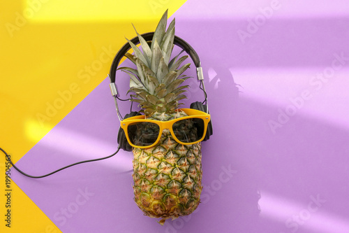 Fresh ripe pineapple with headphones and sunglasses on color background, top view