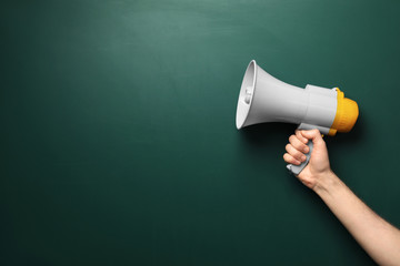 Man holding megaphone near chalkboard