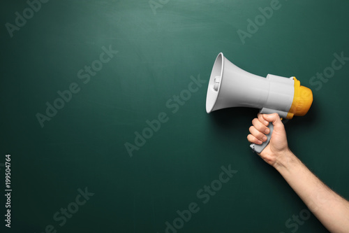 Fotografía  Man holding megaphone near chalkboard