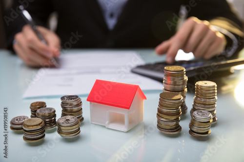 Papiers peints Akt Close-up Of House Model And Stacked Coins On Desk