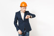 Young irritated dissatisfied businessman in dark suit, protective construction orange helmet looking on clock on hand isolated on white background. Time is running out. Male worker for advertisement.
