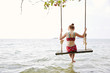 Girl on swing at sea