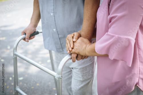 Fotografiet assisting her senior patient who's using a walker for support