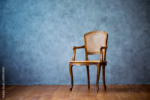 Fotografia old chair on a gray wall background.