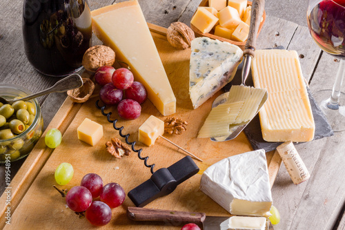 Plakat Paleta wielu rodzajów sera i niektórych winogron, oliwek i wina.