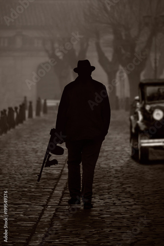 Fotografie, Obraz  Silhouette of a gangster with machine gun, on a street with fog