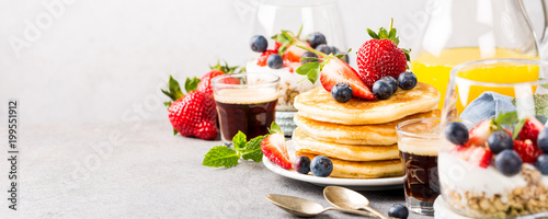 Fotografia Breakfast composition with fresh pancakes and berries on light gray concrete background