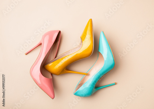 Set of colored women's shoes on beige background