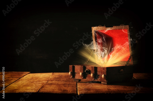 фотография Image of mysterious treasure chest with light and smoke over wooden old table