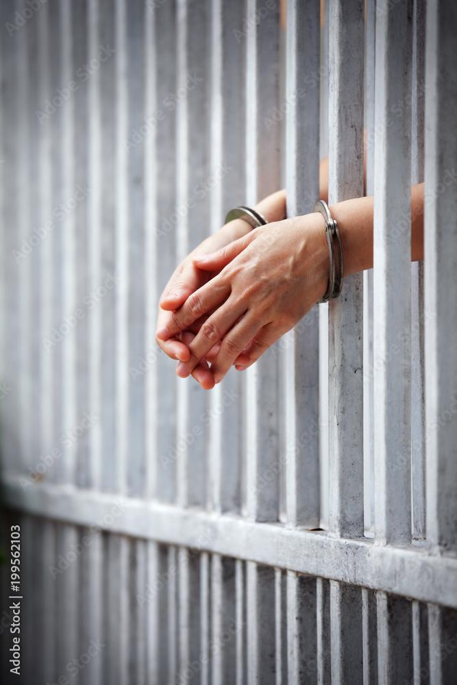 Fototapeta prisoner hands behind jail background.