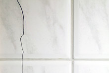 Cracked Tiles On The Bathroom Wall Need Repair. Possible Sign Of Water Damage. Horizontal Image Of Building Problems Concept.