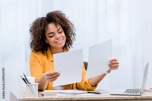 Cuadros en Lienzo smiling young woman doing paperwork at office