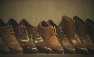 Row of leather mens shoes. Mens shoes, boot sell in store, boutique, shopping mall. Mens shoes concept. Mens fashion, style, quality, leather, leatherette. Shelf with brown mens shoes.