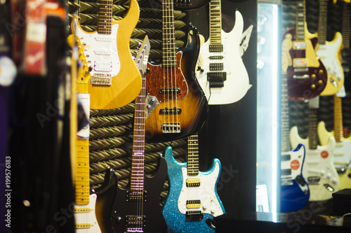 Deurstickers Muziekwinkel Guitars of different colours in music store.