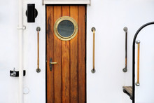Vintage Wooden Brown Door With Round Window On A White Vessel.