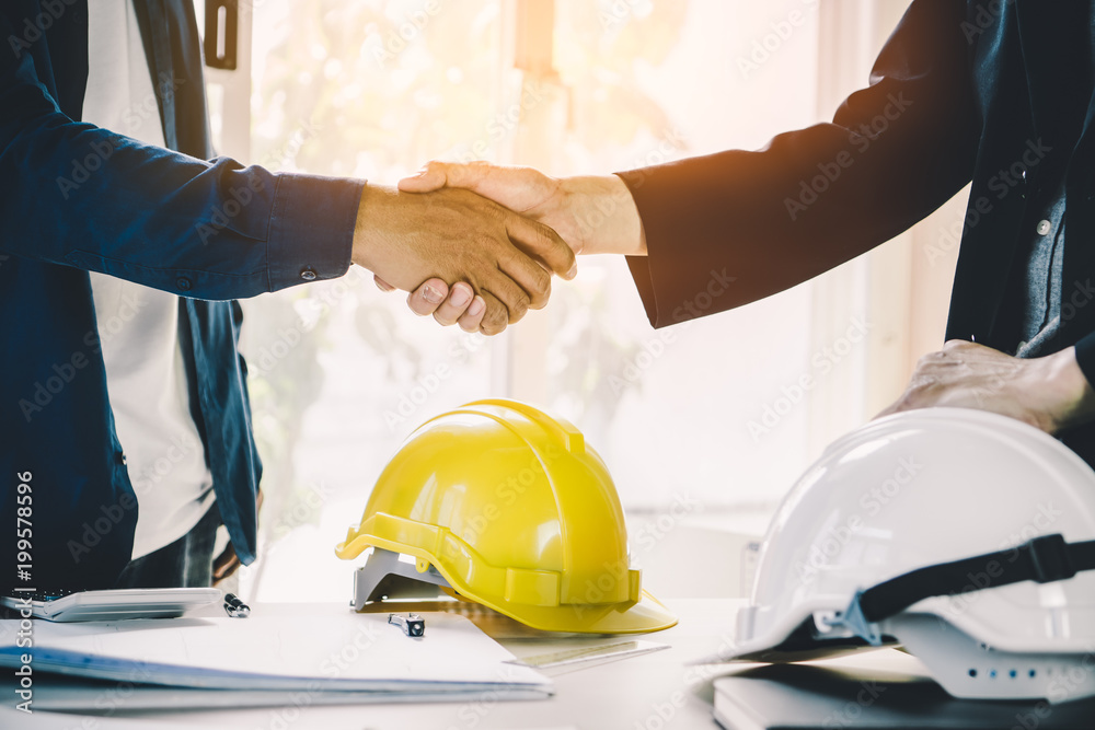 Fototapety, obrazy: Successful deal, male architect shaking hands with client in construction site after confirm blueprint for renovate building.